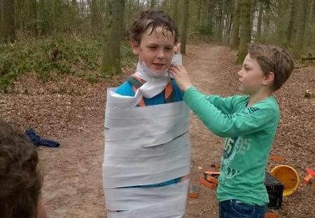 Welpen maken een mummiepak als opdracht voor Levend Ganzenbord